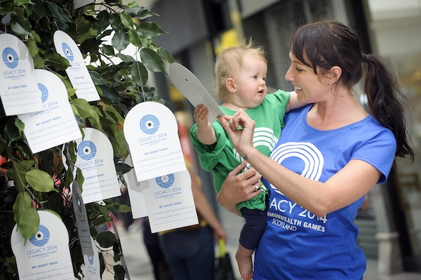 Fourteen month old Rose Patience from Edinburgh hangs her Legacy wish on the tree with the help of Vicki from the Your Legacy tour team.