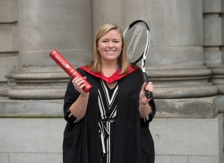 Michelle Moreau on graduation day with a scroll and a tennis racquet
