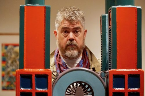 Phill Jupitus behind Paolozzi sculpture