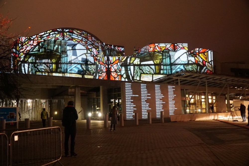Scottish Parliament with projections illuminating the facade