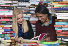Two students surrounded by books