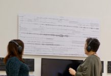 Audio visual exhibition with two people listening with headphones