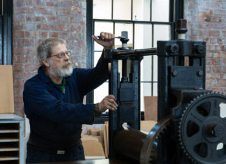 Overalled man working at printing press