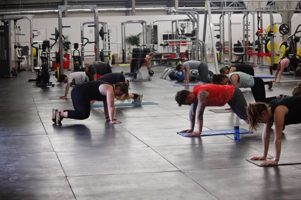 A group of people training hard on floor mats at the gym