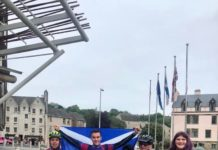 Members of the Hanley family on bikes with Saltire behind posing outside Holyrood