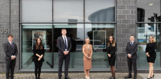 Six young trainees standing in a row in front of a glass-fronted office building