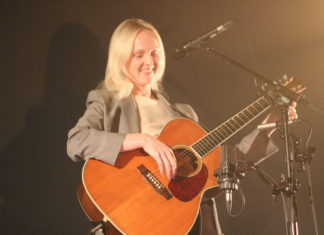 Singer songwriter with guitar on stage at Queen's Hall
